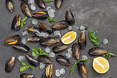 Mussels with lemon and ice, mint are scattered on table.