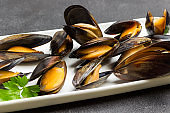 Mussels with open shells on white plate. Shellfish seafood.