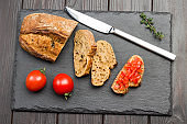 Pieces of bread and knife. Sliced tomato sandwich.