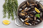 Shellfish Mussels in frying pan.  Rosemary and lemon on table.