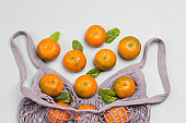 Reusable mesh bag with tangerines.