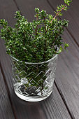 Thyme sprigs in glass. Dark wooden background.