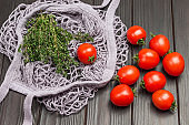 Red chili peppers and thyme twigs in natural reusable mesh bag