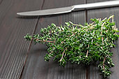 Thyme sprigs. Kitchen knife. Dark wooden background