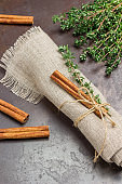 Sprig of thyme and cinnamon stick on linen napkin.