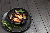 Shrimp and mussels with black rice in bowl.