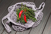 Red chili peppers and thyme twigs in natural reusable cotton mesh bag