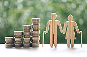 Mutual fund,Love couple senior and stack of coins money on natural green background, Save money for prepare in future and pension retirement concept