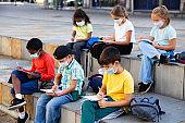 Schoolchildren in face masks during lesson outside school