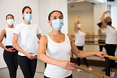 Latin american woman in a protective mask stands holding a barre in a ballet stance