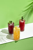 Black currant, orange and raspberry lemonade drink over green background. White table with sunlight and palm leaf hard shadow. Summer, tropical and juicy concept