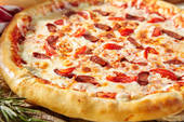 Spicy Sausage Italian Pizza with tomato, mozzarella cheese, sausage slice. Homemade pizza on baking paper with food ingredients on wooden table. Fast food or junk food pizza dinner rustic style.