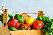 Fresh vegetables, lemon and parsley in wooden crate.