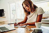 Caucasian student working from home writing on note pad with pen sitting with coffee and laptop