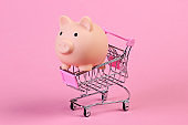Shopping trolley with piggy bank close-up on a pink pastel background