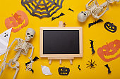 Mini blank chalk board with copy space and halloween decor on yellow background. Trick or treat. Flat lay
