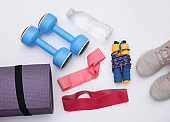 Flat lay composition of fitness outfit, accessories on white background. Healthy lifestyle, sport concept. Top view