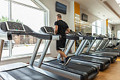 Handsome muscular male bodybuilder is exercising on a treadmill in a modern gym. Cardio workout