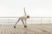 Slim fit blonde woman in sportswear warming up before training on the beach. Healthy lifestyle, outdoor sports concept