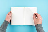 person turning page of blank white page hardcover book
