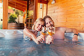 Couple making a toast and relaxing in a hot tub