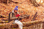 Woman reading a book in the forest