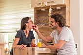 Couple relaxing while having breakfast at home