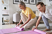 Sporty fit middle aged old couple hands rolling or unrolling yoga pilates mat at home. Seniors fitness exercises, elder health and body care training, mature people active lifestyle concept, close up.