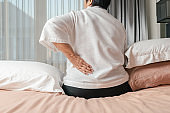 Old woman back pain at home, health problem concept