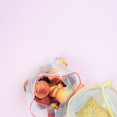 Peaches and melon are packed in grocery mesh on a pink background, copy space. Zero waste