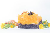Citrus soap with orange and anise on a white background with herbs, autumn spa concept.