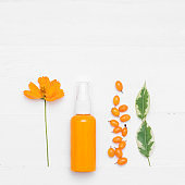 Natural cosmetic product. Cosmetic cream with sea buckthorn on a white background. The concept of natural organic cosmetics and skin care. Flat lay, minimal style.