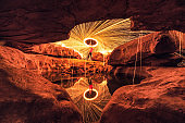 Man wielding spark fire swirl in stone hole cave and pond reflection in the night at Sam Phan Bok
