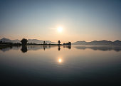Scenery of sunrise on mountain range with fog in the morning at reservoir