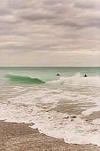 Surfers Surfing on Teal Ocean Waves Sweeping Across the Juno Beach, Florida Seashore at Mid-Day in January of 2021