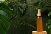 Facial serum fluid cosmetic oil in the bottle with freshness green tropical leaves and water drops on green background. Eco organic natural beauty skincare product. Dermatology and cosmetology