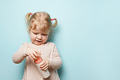 child girl holding a bottle in the hands with shower gel on blue background, body care products for children
