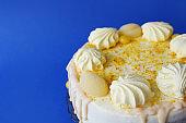 Lemon cake with sugar powder and marshmallows on blue background
