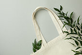 Eco bag and twigs on light gray background