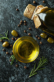 Bottle and bowl with olive oil and spices on black smokey background
