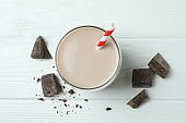Glass of chocolate milkshake and chocolate pieces on white wooden table