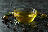 Bowl of olive oil, olives, pepper and rosemary on black smokey background