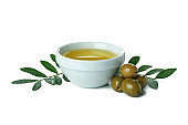 Bowl of olive oil, twigs and olives isolated on white background