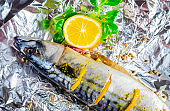 Raw mackerel with lemon and spices on foil