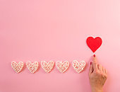 White hearts line on pink background, hand with red heart.