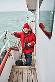 Man standing at the deck of the boat while fishing