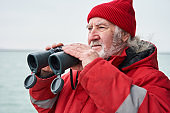 Fishing ship dressed in protective coat looking through binoculars