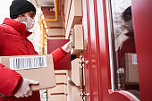 Courier deliver parcels in brown cardboard boxes to the door
