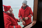 Two mans drinking tea at the deck of the boat
