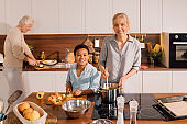 Grandmother and her multiracial son looking to the camera while preparing soup
